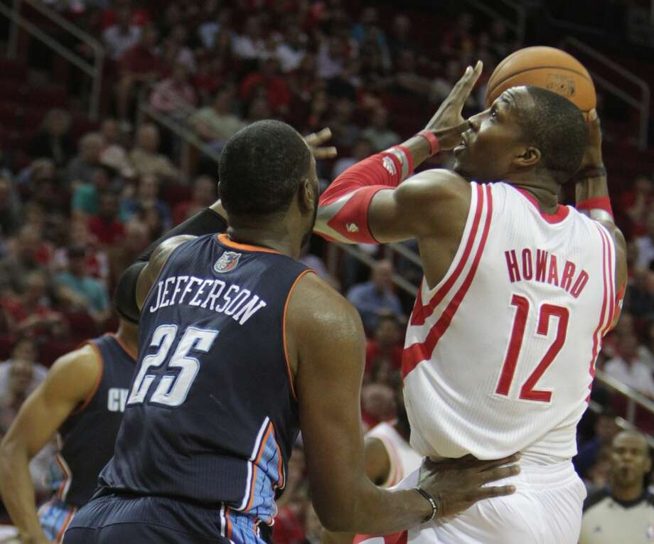 Rockets center Dwight Howard looks to shoot over Al Jefferson of the Bobcats. Photo: James Nielsen, Houston Chronicle