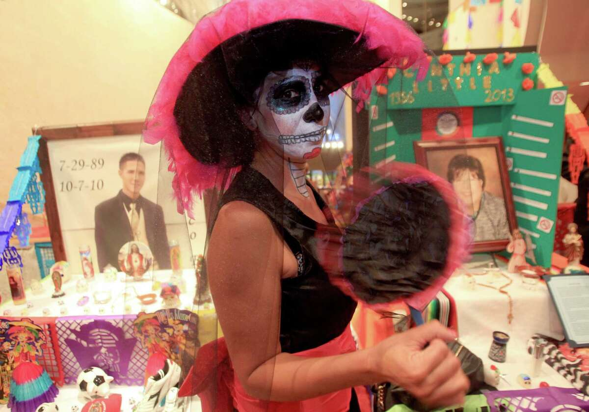 Alexandra Sanchez is dressed as 'La Catrina' near the altars dedicated to friends and volunteers of Bonding Against Adversity during the The Houston Symphony and the Mexican Consulate of Houston display of Day of the Dead altars in Jones Hall on Wednesday, Oct. 30, 2013, in Houston.