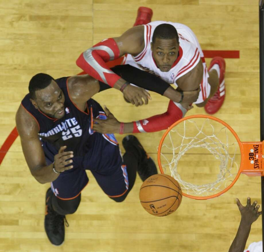 Rockets center Dwight Howard jockeys for position against Bobcats center Al Jefferson. Photo: James Nielsen, Houston Chronicle