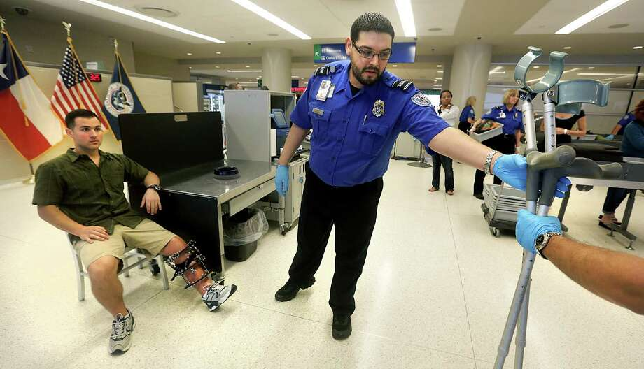 Robert Riza (center), a TSA agent, hands off crutches belonging to Air Force Master Sgt. Jeremy Maddamma (left) to be X-rayed Wednesday as Maddamma poses as a traveling passenger at the San Antonio International Airport. Photo: Bob Owen / San Antonio Express-News