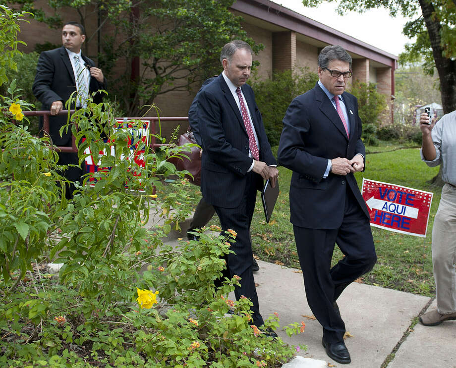 "Gov. Rick Perry leaves an Austin public library after casting his vote early. ""I gave my driver's license and it went as advertised,"" he said. Photo: Erika Rich / Austin American-Statesman"
