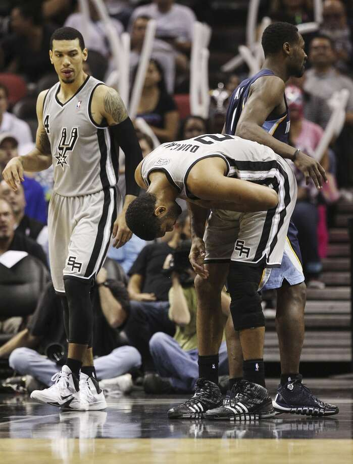 Spurs' Tim Duncan (21) bends over in pain after defending against Memphis Grizzlies' Tony Allen (09) in the second half of the home opener at the AT&T Center on Wednesday, Oct. 30, 2013. Duncan was injured on the play and never returned after leaving to the locker room. Spurs defeated the Grizzlies, 101-94.  (Kin Man Hui/San Antonio Express-News) Photo: San Antonio Express-News