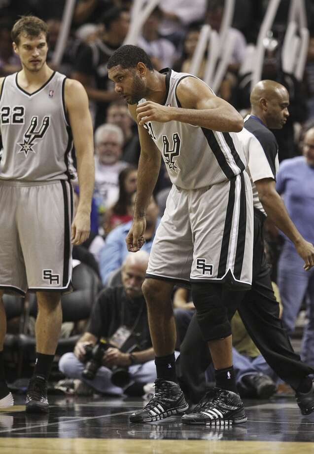 Spurs' Tim Duncan (21) appears in pain after defending against Memphis Grizzlies' Tony Allen (09) in the second half of the home opener at the AT&T Center on Wednesday, Oct. 30, 2013. Duncan was injured on the play and never returned after leaving to the locker room. Spurs defeated the Grizzlies, 101-94.  (Kin Man Hui/San Antonio Express-News) Photo: San Antonio Express-News