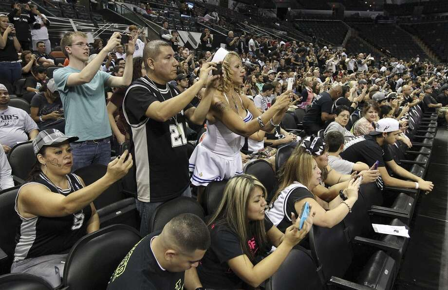 Spurs fans get take photos of their team during shoot around before the home opener against the Memphis Grizzlies at the AT&T Center on Wednesday, Oct. 30, 2013. (Kin Man Hui/San Antonio Express-News) Photo: San Antonio Express-News