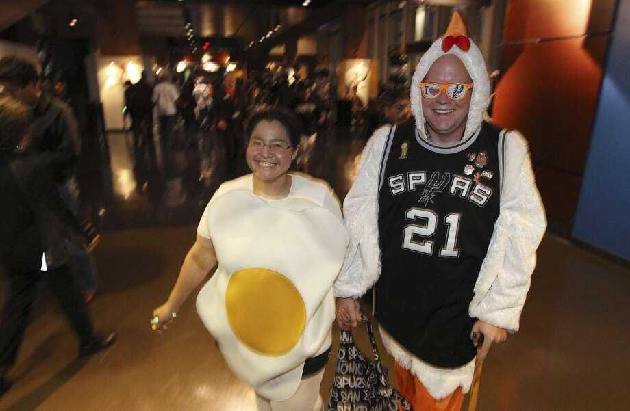 Spurs fans Michael and Victoria Harmon wear costumes as they attend the home opener against the Memphis Grizzlies at the AT&T Center on Wednesday, Oct. 30, 2013. (Kin Man Hui/San Antonio Express-News) Photo: San Antonio Express-News