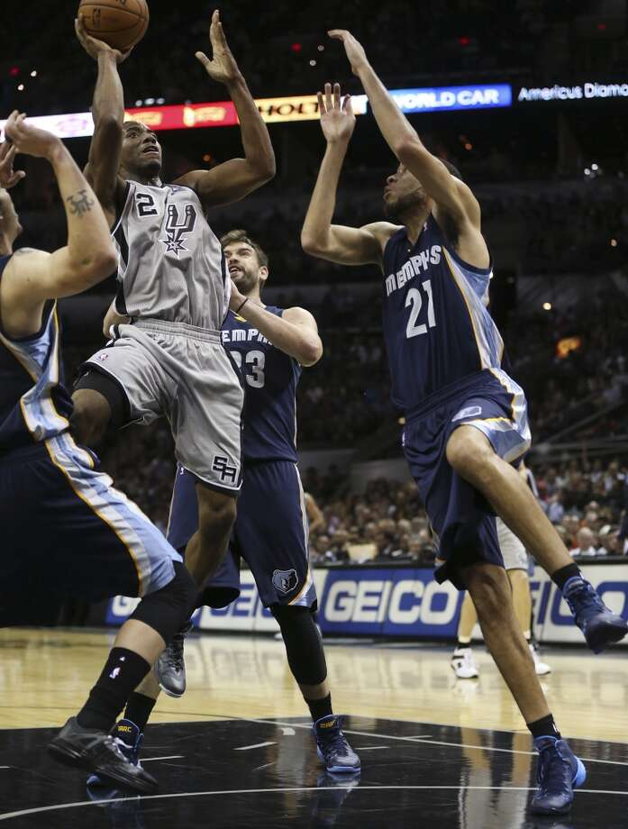 San Antonio Spurs' Kawhi Leonard drives through Memphis Grizzlies' Marc Gasol, (33),  and Tayshaun Prince, (21), during the first half at the AT&T Center, Wednesday, Oct. 30, 2013. Photo: San Antonio Express-News