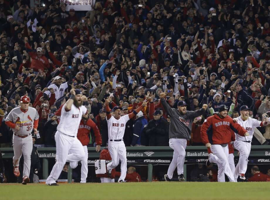 Red Sox players rush onto the field after defeating the Cardinals. Photo: Elise Amendola, Associated Press