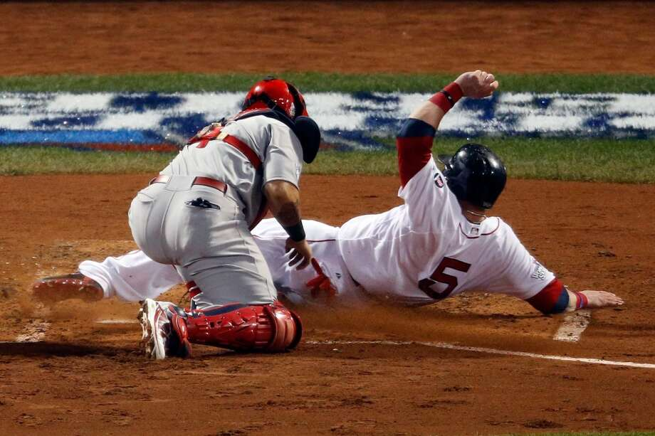 Jonny Gomes #5 of the Red Sox slides safely into home plate as Yadier Molina #4 of the Cardinals tries to make the play. Photo: Jim Rogash, Getty Images