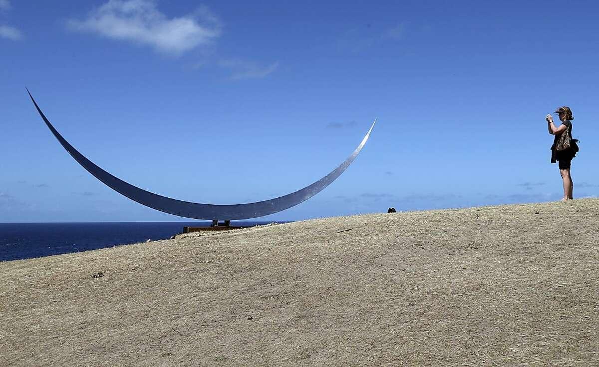 A woman photographs a sculpture by Australian artist Matthew Harding called