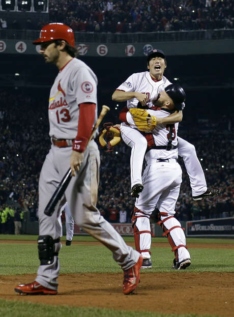 Closer Koji Uehara (middle) rejoices with catcher David Ross after striking out St. Louis' Matt Carpenter (left), clinching the World Series in Boston for the first time since 1918. Photo: Matt Slocum / Associated Press