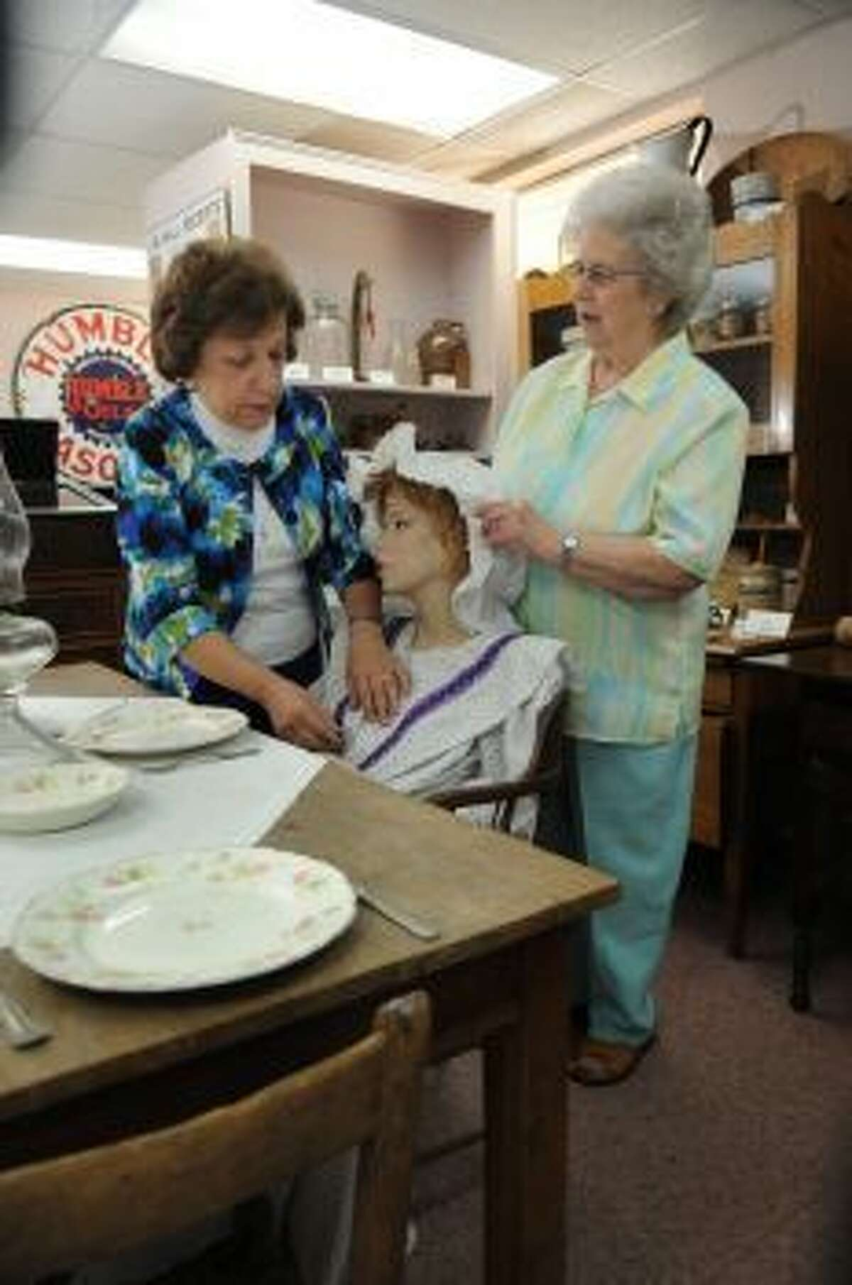 Humble Museum board President Nancy Coker, right, prepares an exhibit with the help of museum worker Jerri Christian.