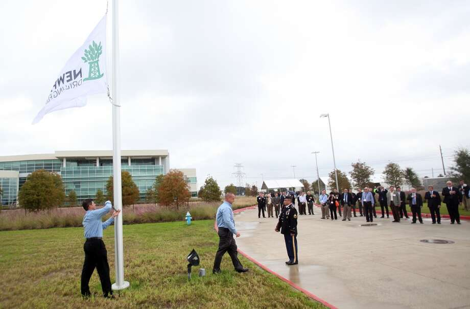 The company flag flaps in the wind as the U.S. Army Color Guard conducts the flag raising ceremony at Newpark Drilling Fluids' new technology center, which hosted a grand opening on Wednesday, Oct. 30, 2013, in Katy. Photo: Mayra Beltran, Houston Chronicle