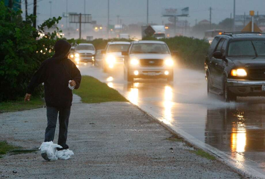 A pedestrian uses plastic bags to keep his feet dry as he walks along the feeder road near Gulf Freeway early Thursday morning. Photo: Cody Duty, Houston Chronicle