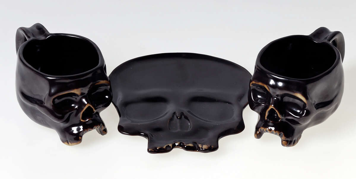 The skull has been a bad-to-the-bone symbol of death. But the Halloween favorite has gone from scary to stylish, no longer a mere seasonal statement, and is desired by edgy fashionistas - Michael Quintanilla. In this photo: Detail of black skull mugs, $9.95 each with Black Skull plate, $12.95, Williams Sonoma.