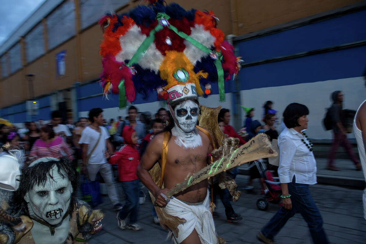 Revelers dance through the streets in traditional costumes at the start of the Day of the Dead festival known in Spanish as Dia de Muertos October 30, 2013 in Oaxaca, Mexico.