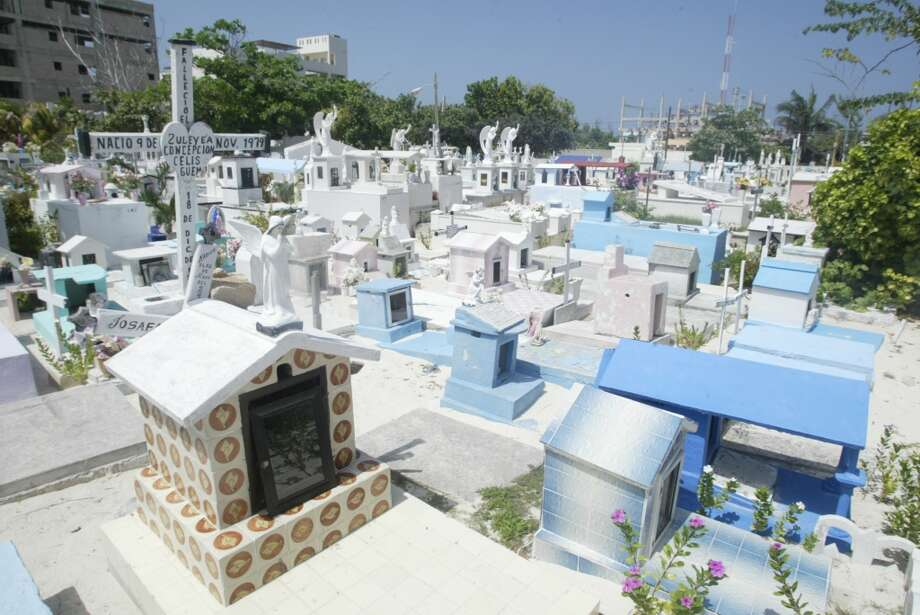 The old cemetery on Isla Mujeres is a bizarre collection of crypts and tombs, seemingly placed without rhyme or reason. It is nearly impossible to get from one side to the other without stepping or climbing on graves. Photo: Spud Hilton, The Chronicle