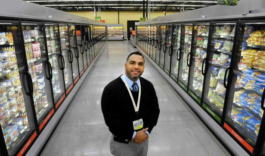 Store manager Juan Rivera stands in the frozen foods section at the Walmart Neighborhood Market on Thursday, Oct. 31, 2013 in Niskayuna, N.Y. The new grocery store opens Friday.  (Paul Buckowski / Times Union) Photo: Paul Buckowski / 00024406A