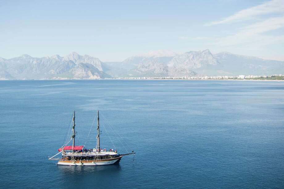 A sailboat cruises along the Mediterranean coastline in Antalya, Turkey. Photo: Jody Schmal