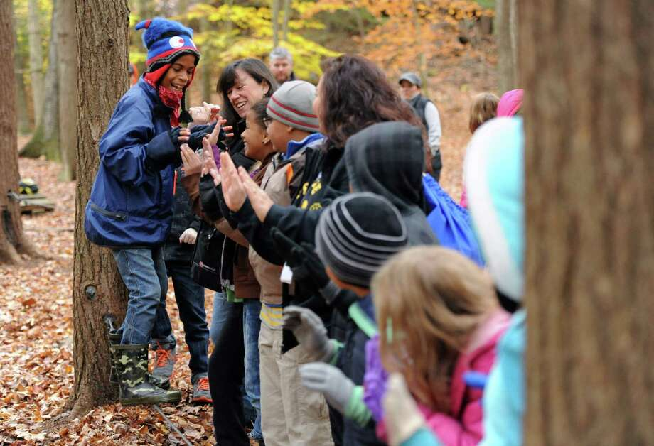 Fifth-grader Anderson Gabriel, left, walks along a wire while using the hands of classmates for support and balance during a team building activity from the Pembroke School fifth graders' weeklong stay at the Nature's Classroom camp in Colebrook, Conn. on Wednesday, Oct. 30, 2013.  Sixty students camped in cabins for the week with teacher Rebecca Migiano, spending their days doing anything from hiking in the woods, to team building activities, to improvisational sketch comedy, all while accompanied by the instructors at Nature's Classroom. Photo: Tyler Sizemore / The News-Times
