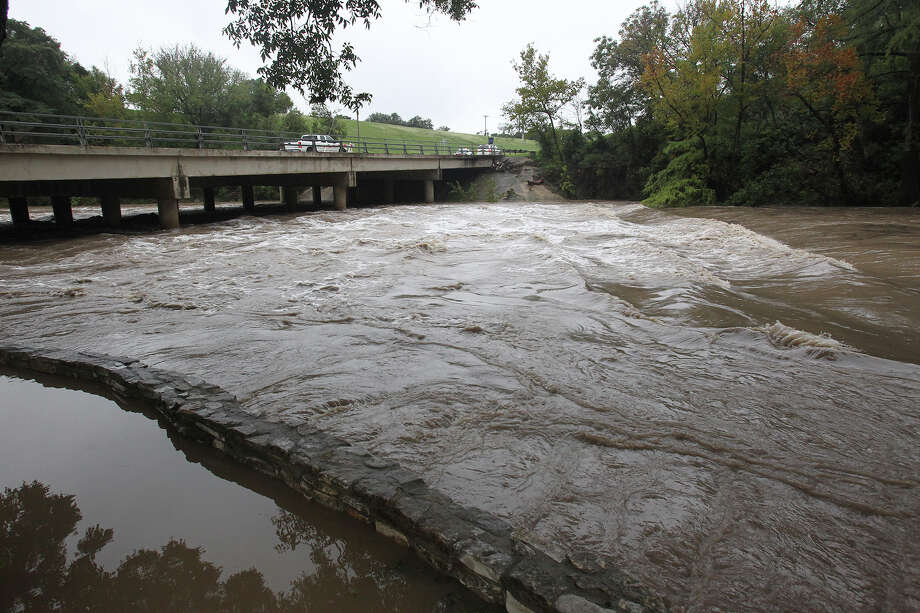 Water rushes under the Commons Street bridge as the Guadalupe River and Comal rivers flow over their banks in New Braunfels  on October 31, 2013. Photo: TOM REEL
