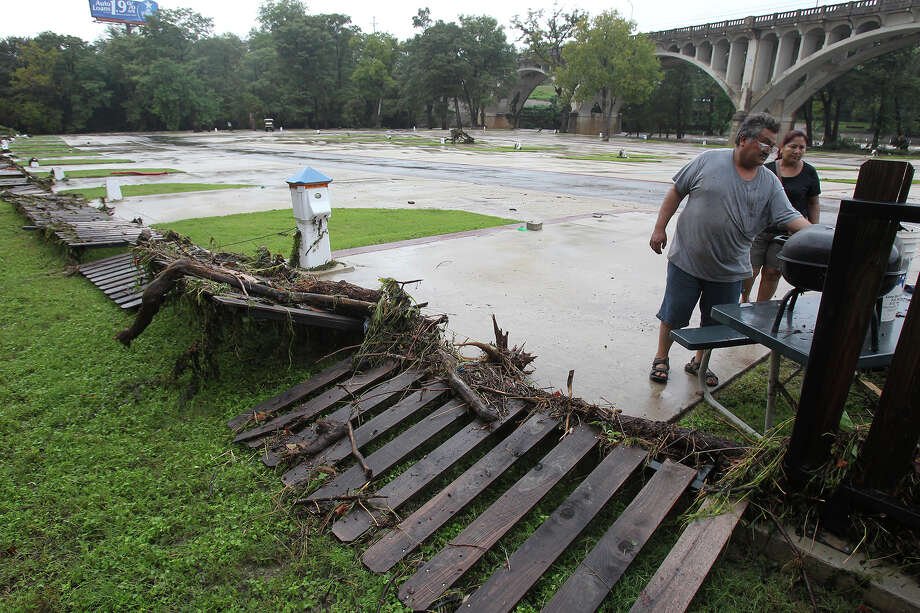 A couple helps in the clean up of  debris at River Ranch RV Resort after the Guadalupe River and Comal rivers flow over their banks in New Braunfels  on October 31, 2013. Photo: TOM REEL