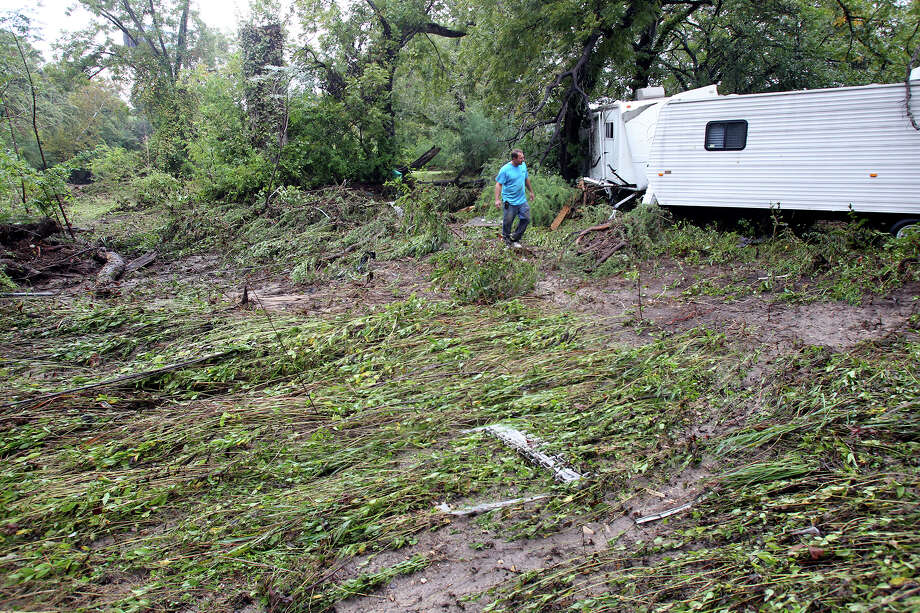 Ken Posey inspects an RV trailer  nestled downstream from the River Ranch RV Resort after the Guadalupe River and Comal rivers flow over their banks in New Braunfels  on October 31, 2013. Photo: TOM REEL