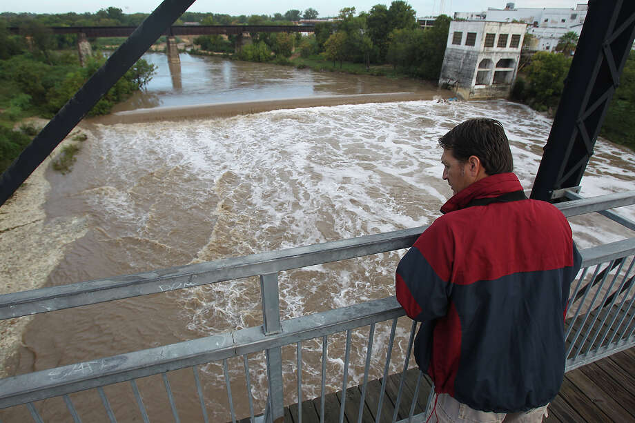 A spectator (would not give name) watches flood water rush under the Faust Street Bridge after Guadalupe River and Comal rivers flow over their banks in New Braunfels  on October 31, 2013. Photo: TOM REEL