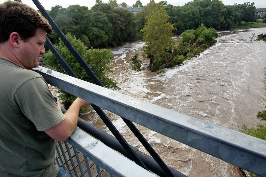 Karl Toepperwein  watches flood water rush under the Faust Street Bridge after Guadalupe River and Comal rivers flow over their banks in New Braunfels  on October 31, 2013. Photo: TOM REEL