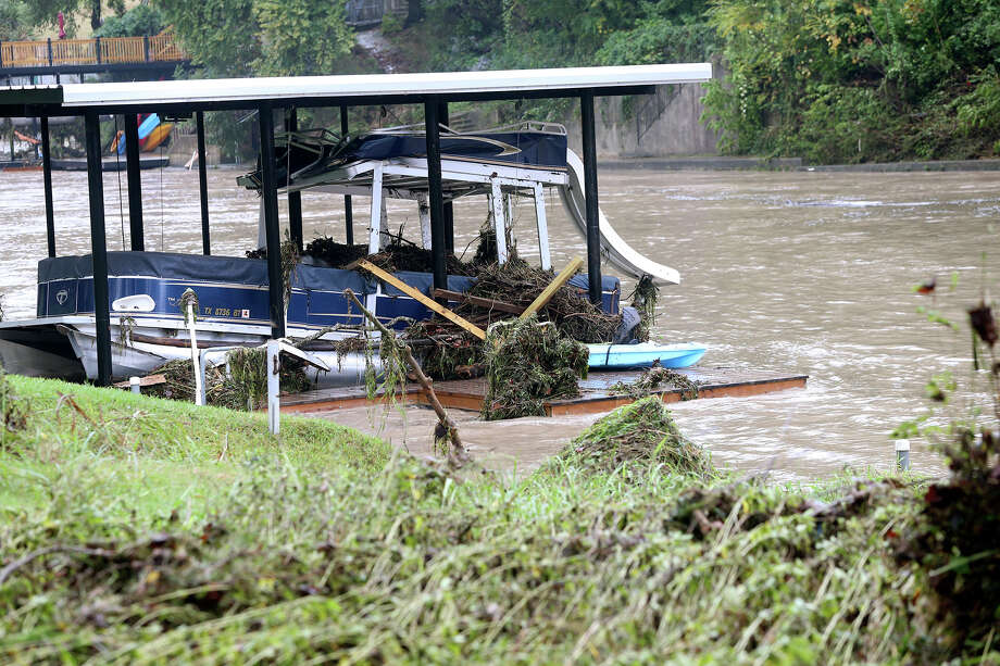 A docked boat stayed in place but was damaged as the Guadalupe River and Comal rivers flow over their banks in New Braunfels  on October 31, 2013. Photo: TOM REEL