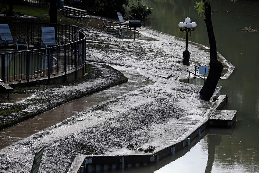 Normally green, grassy banks on the Comal River are covered with mud as the water rose overnight in flash flooding in New Braunfels on October 31, 2013.