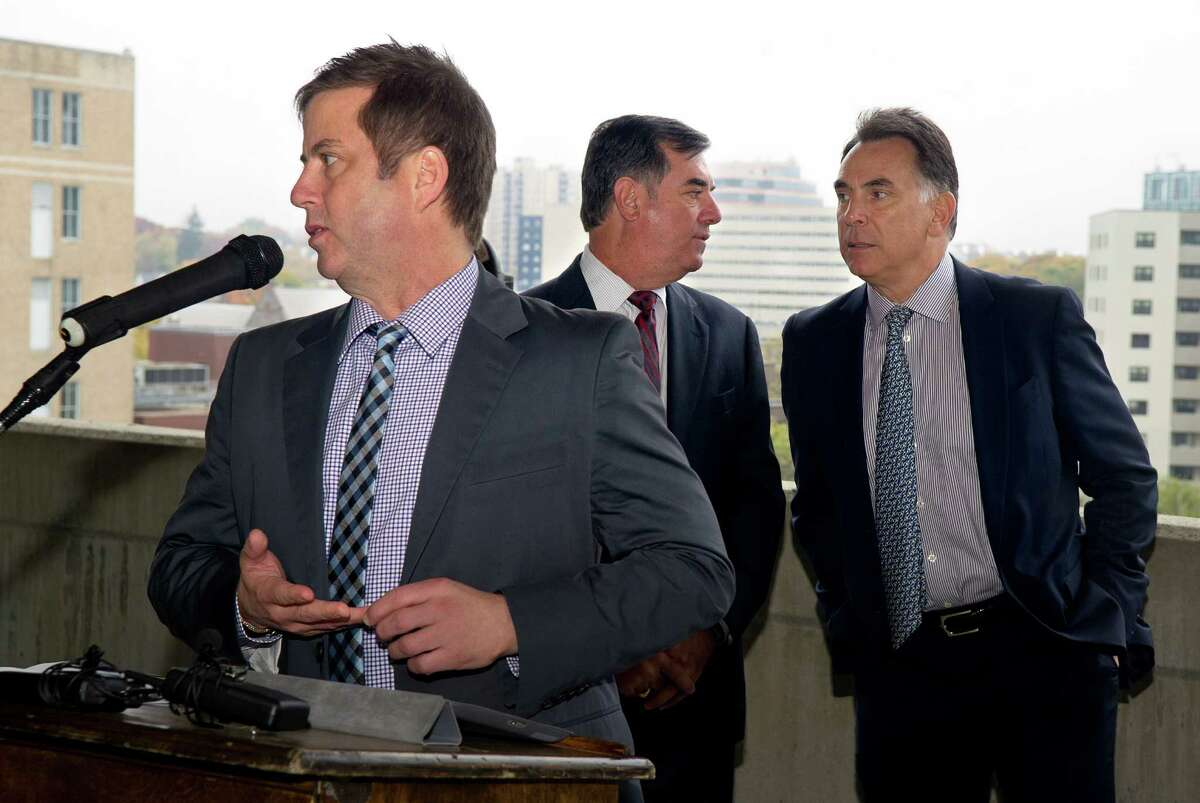 David Barry of Ironstate Development speaks as Mayor Michael Pavia, center, talks with Tom Rich, right, during a press conference on Oct. 31, 2013 to announce a development deal has been reached for the downtown site in Stamford, Conn..