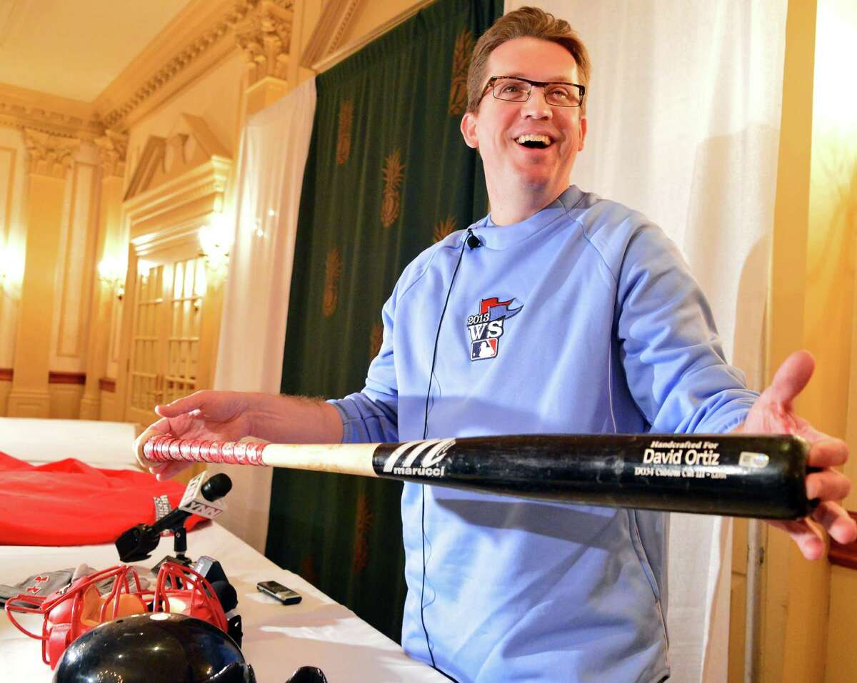 Brad Horn, director of education at the Baseball Hall of Fame, holds David Ortiz's bat from game 5 of the 2013 World Series on Thursday, Oct. 31, 2013, in Colonie, NY. Artifacts from the series were displayed during a news conference at the Desmond in Colonie, N.Y. They are en route to Cooperstown. (John Carl D'Annibale / Times Union)
