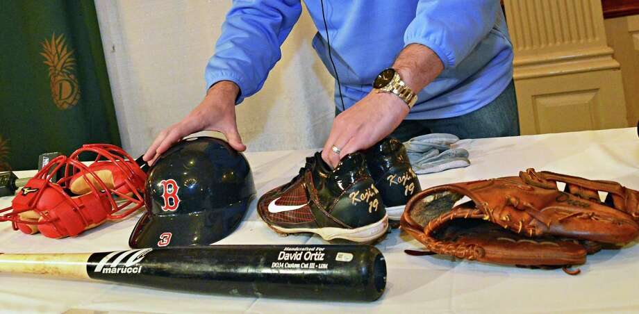 Brad Horn, director of education at the Baseball Hall of Fame, lays out a catcher's mask and helmet from David Ross, cleats from pitcher Koji Uehara, David Ortiz's bat, and Stephen Drew's glove, which were among the 2013 World Series artifacts en route to Cooperstown Thursday, Oct. 31, 2013. The artifacts were displayed during a news conference at the Desmond Hotel in Colonie, N.Y. (John Carl D'Annibale / Times Union) Photo: John Carl D'Annibale / 00024461A