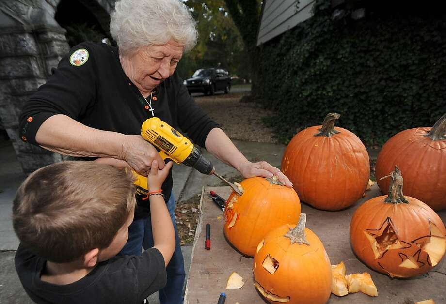 Oh, he'll talk. You'll see: Betty Dillow helps her 5-year-old grandson torture carve a pumpkin in Bristol, 