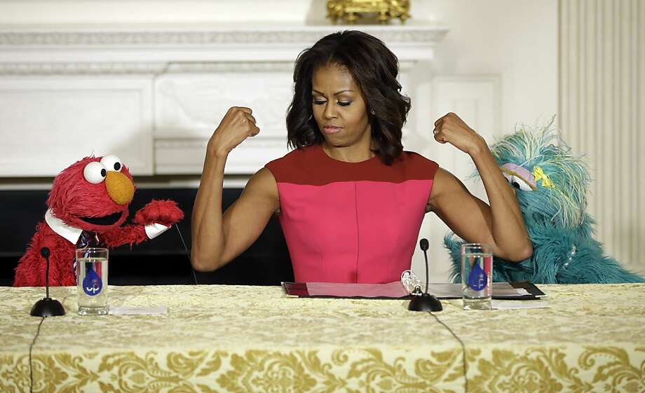 "Muscle me, Elmo:Michelle Obama flexes for ""Sesame Street"" characters Elmo and Rosita at a White House event promoting fresh fruit and vegetable consumption. Photo: Pablo Martinez Monsivais, Associated Press"