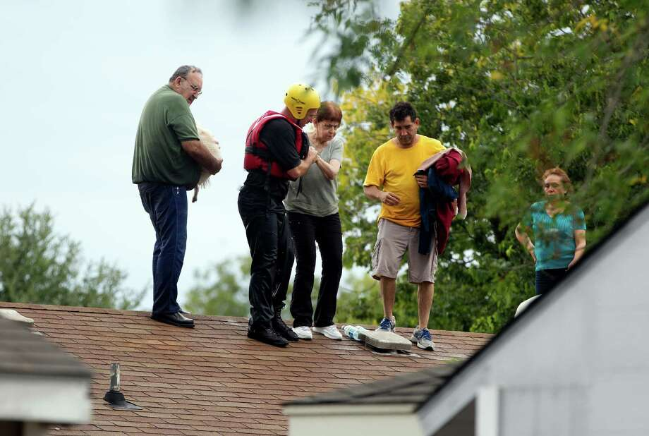 People are rescued from a home's rooftop  in southeast Austin, Texas, on Thursday, Oct. 31, 2013. Heavy overnight rains brought flooding to the area. The National Weather Service said more than a foot of rain fell in Central Texas, including up to 14 inches in Wimberley, since rainstorms began Wednesday.  (AP Photo/The Austin American-Statesman, Deborah Cannon) AUSTIN CHRONICLE OUT, COMMUNITY IMPACT OUT, INTERNET MUST CREDIT PHOTOGRAPHER AND STATESMAN.COM, NO SALES Photo: Deborah Cannon, Associated Press / American-Statesman