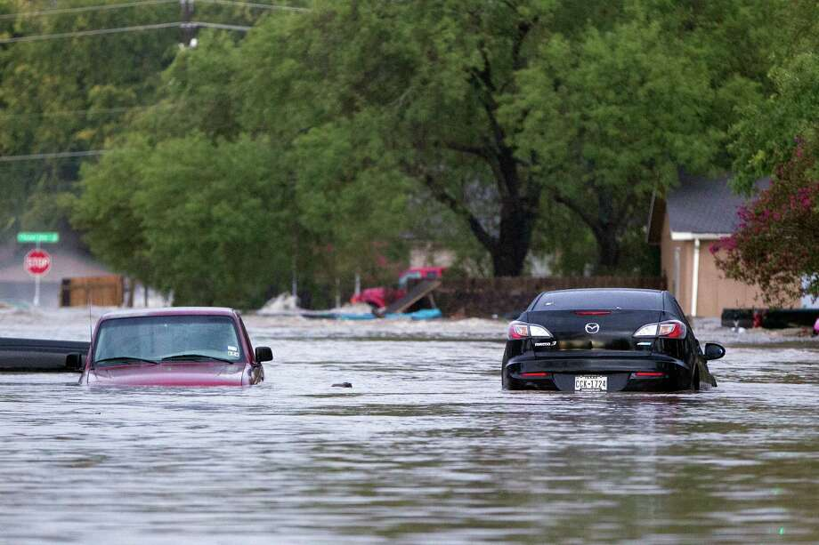 Cars are partially submerged on Quicksilver Blvd in southeast Austin, Texas, on Thursday, Oct. 31, 2013. Heavy overnight rains brought flooding to the area. The National Weather Service said more than a foot of rain fell in Central Texas, including up to 14 inches in Wimberley, since rainstorms began Wednesday.  (AP Photo/The Austin American-Statesman, Deborah Cannon) AUSTIN CHRONICLE OUT, COMMUNITY IMPACT OUT, INTERNET MUST CREDIT PHOTOGRAPHER AND STATESMAN.COM, NO SALES Photo: Deborah Cannon, Associated Press / American-Statesman