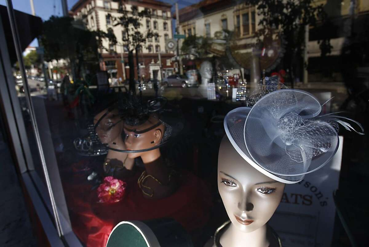 Hats are displayed in the window of Mrs. Dewson's Hats on Fillmore street where the surrounding neighborhood is reflected in the windows in San Francisco, Calif. on Monday, September 21, 2009.