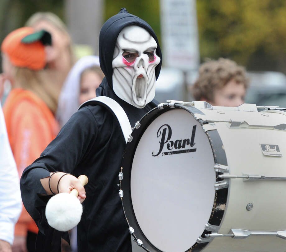 Dressed as a ghost, Thomas Cass, 10, a fifth-grader, bangs the bass drum while marching in the Old Greenwich School's annual Halloween parade in Old Greenwich, Thursday, Oct. 31, 2013. Photo: Bob Luckey / Greenwich Time
