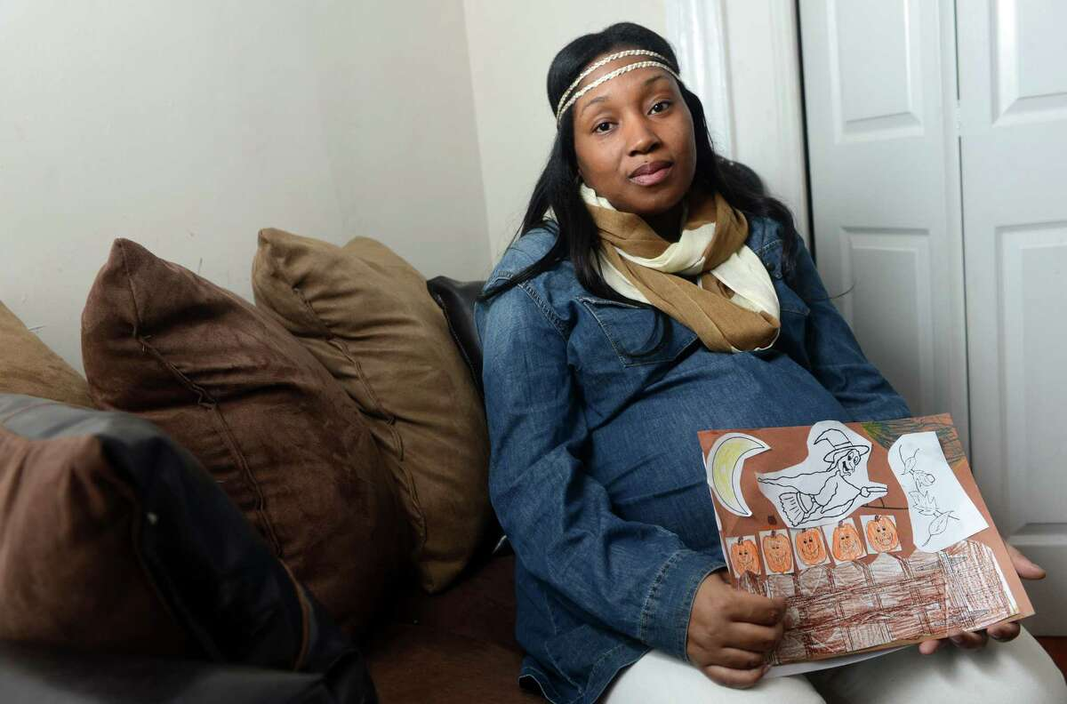 Nakeya Hargrove, mom of one of the two students Carmen Perez Dickson is accused of dragging through the hall at Tisdale School, holds some of her child's school work Thursday, Oct. 31, 2013 at her home in Bridgeport, Conn. She is not happy Dickson was suspended and not fired.