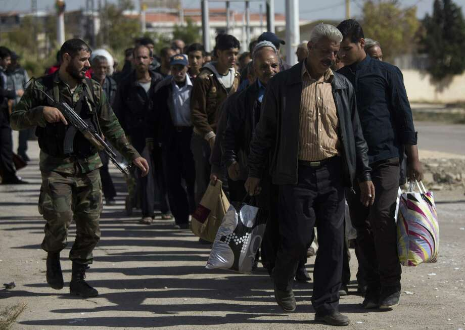 A Syrian soldier escorts men from the rebel-held suburb of Moadamiyeh to government-held territory in Damascus. The involvement of jihadist rebels has complicated the nation's tragedy. Photo: Dusan Vranic / Associated Press