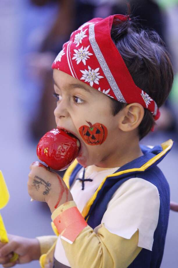 Finian Giles, 3, enjoys a candy apple Photo: J. Patric Schneider, For The Chronicle