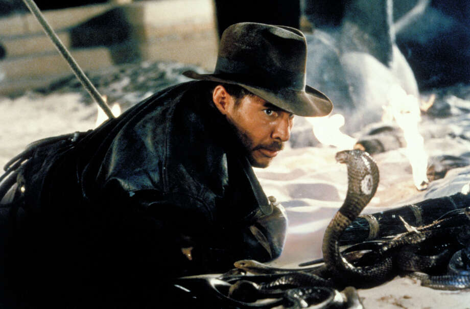 """Actor Harrison Ford comes face-to-face with a cobra in a scene from the Indiana Jones adventure """"Raiders of the Lost Ark,"""" in this undated promotional photo. The four-disc DVD set of """"The Adventures of Indiana Jones,"""" slated to hit shelves Tuesday, Oct. 21, 2003, contains """"Raiders of the Lost Ark,"""" """"Indiana Jones and the Temple of Doom,"""" """"Indiana Jones and the Last Crusade,"""" plus DVD extras that include a two-hour """"making-of"""" documentary. (AP Photo/LucasFilms) / PARAMOUNT PICTURES"""