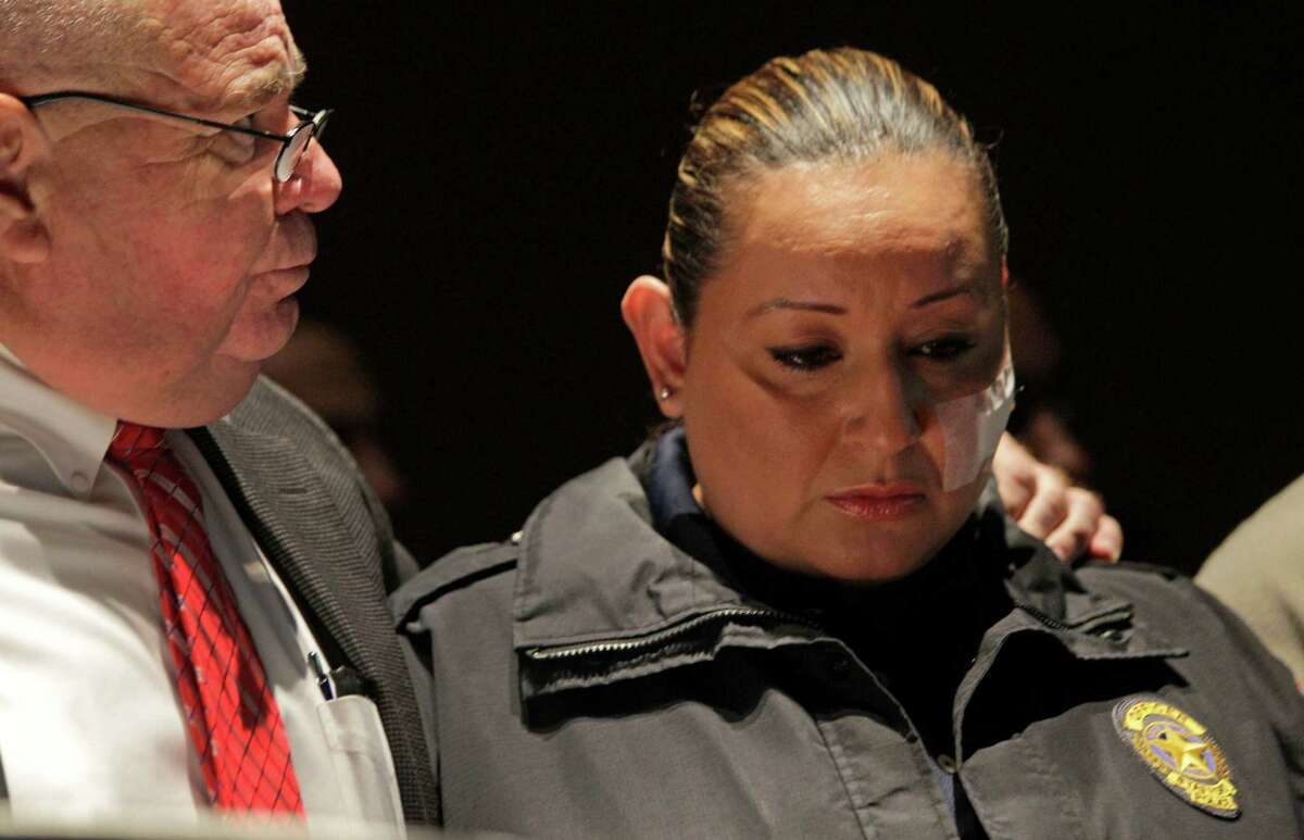 Stafford Police Chief B.R. Krahn, left, comforts and keeps a hand on the shoulder of Stafford Police officer Ann Carrizales, right, as the dash cam video of her being shot is shown during media conference at the Stafford Centre, 10505 Cash Road, Thursday, Oct. 31, 2013, in Stafford. Officer Carrizales was shot and wounded during a traffic stop on Oct. 26.