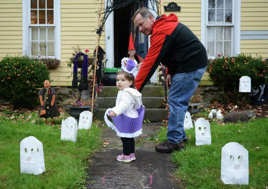 Teagan Burke, 1, trick-or-treats dressed as a teacup with her grandpa Joe Skrzypczak, of Newtown, at Halloween trick-or-treat night in Newtown, Conn. on Thursday, Oct. 31, 2013.  After being cancelled the last two years due to poor weather conditions, hundreds of Newtown children and parents came out in costume this year, going door to door down Main Street. Photo: Tyler Sizemore / The News-Times