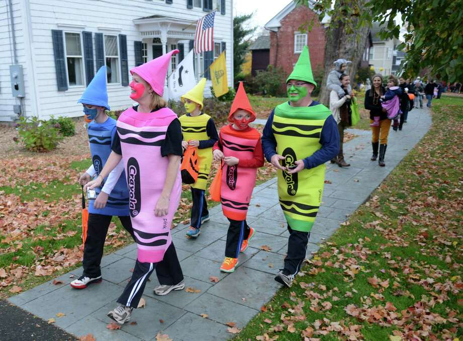 Dressed as a pack of Crayons, the Berard family, of Newtown, walks down the street during Halloween trick-or-treat night in Newtown, Conn. on Thursday, Oct. 31, 2013.  After being cancelled the last two years due to poor weather conditions, hundreds of Newtown children and parents came out in costume this year, going door to door down Main Street. Photo: Tyler Sizemore / The News-Times