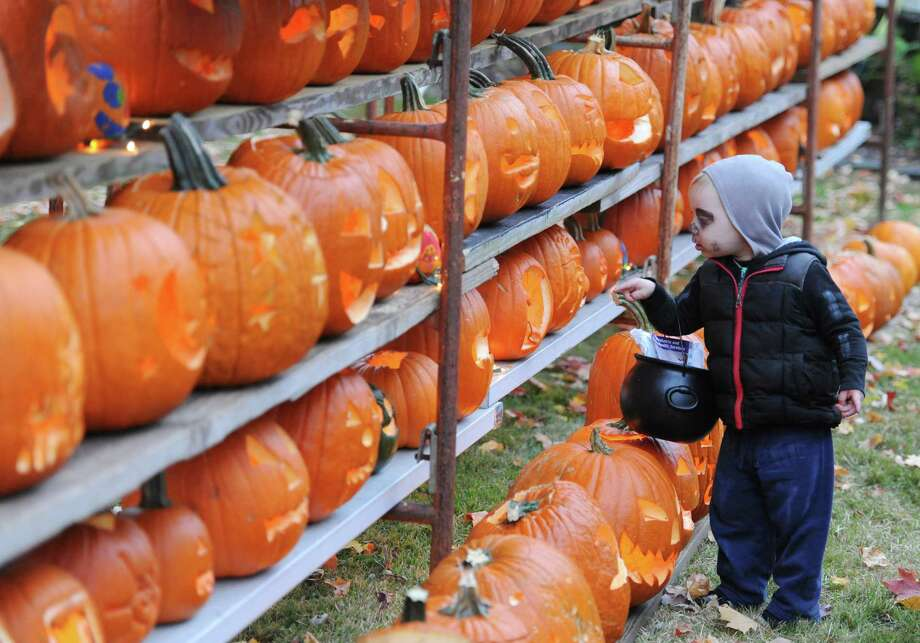 Ben Aldrich, 2, of Bethlehem, Conn., looks at a row of jack-o'-lanterns during Halloween trick-or-treat night in Newtown, Conn. on Thursday, Oct. 31, 2013.  After being cancelled the last two years due to poor weather conditions, hundreds of Newtown children and parents came out in costume this year, going door to door down Main Street. Photo: Tyler Sizemore / The News-Times