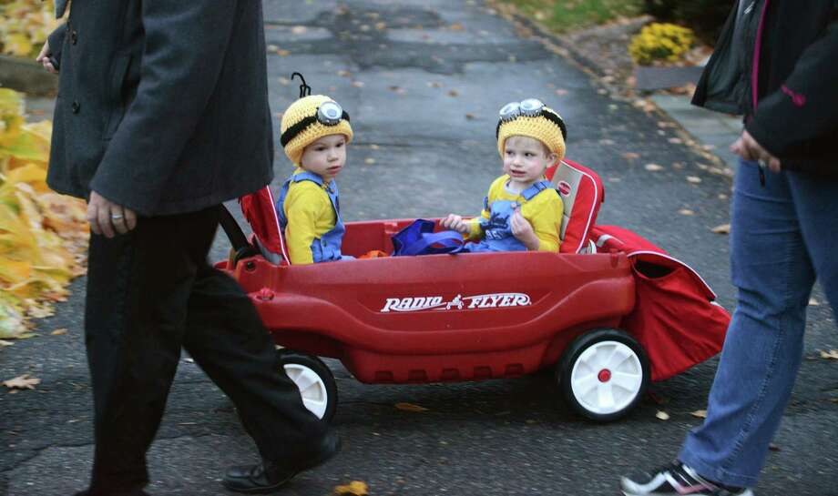 "Dressed as minions from ""Despicable Me,"" Colten and Connor Gagne, 1, of Newtown, ride in a wagon during Halloween trick-or-treat night in Newtown, Conn. on Thursday, Oct. 31, 2013.  After being cancelled the last two years due to poor weather conditions, hundreds of Newtown children and parents came out in costume this year, going door to door down Main Street. Photo: Tyler Sizemore / The News-Times"
