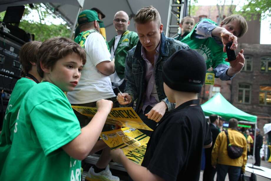 Musician Macklemore signs autographs before he takes the stage during a rally to bring back the Seattle SuperSonics on Thursday, June 14, 2012. An estimated 6,000 people packed into Occidental Park to show support for bringing back the team. (Joshua Trujillo, seattlepi.com) Photo: JOSHUA TRUJILLO