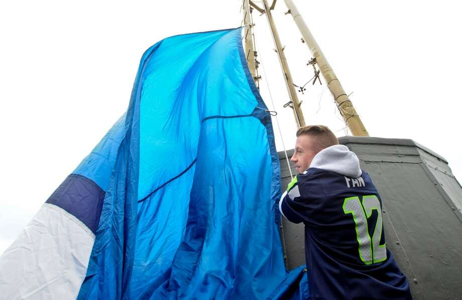 Macklemore helps raise the 12th Man flag atop Seattle's Space Needle on Jan. 4, 2013. The flag was raised in honor of the Seahawks' first playoff game against the Redskins in Washington, D.C. (Photo by Lindsey Wasson)